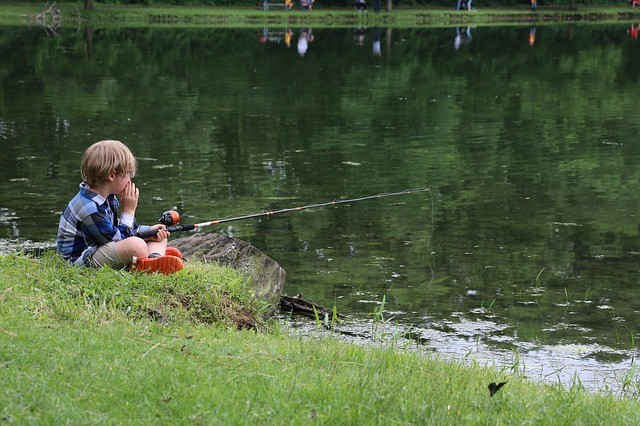 child fishing a pond